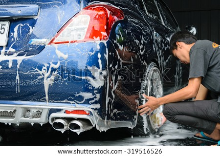 Bangkok, Thailand - June 28, 2015 : Blue car washing by hand using a foam preparation for polishing. - stock photo