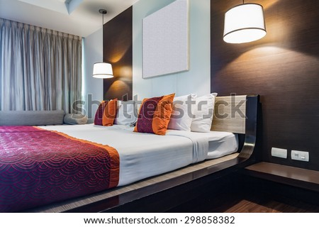 BANGKOK THAILAND - JUNE 18 : Red pillow on double bedroom with white bed sheet and lamp light on, in Spring Field at Sea hotel in Cha-am Phetchaburi, Thailand on June 18, 2015 - stock photo