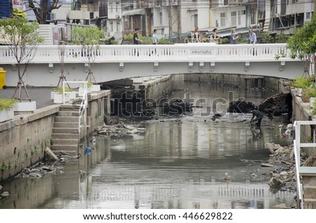 BANGKOK, THAILAND - JUNE 28 :  Trash keeper thai man collect garbage in underwater at wastewater and pollution water in canal for sale on June 28, 2016 in Bangkok, Thailand