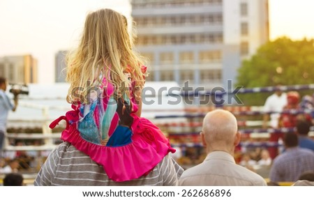 BANGKOK THAILAND -MAR 16 : Little girl ride her father's neck into see the World Martial Arts Council Games Open and Festival on MARCH 12-22, 2015 at Indoor Stadium Hua Mak in Bangkok Thailand - stock photo