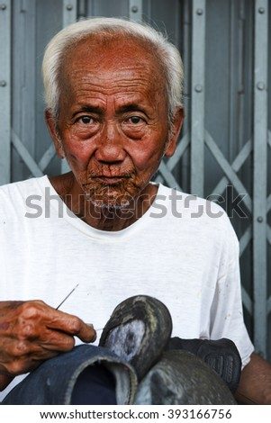 BANGKOK, THAILAND - MARCH 18, 2016: An old man, a shoemaker employed by the roadside on March 18, 2016 in Bangkok, Thailand.