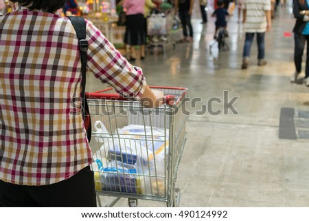 Bangkok, Thailand - March 15, 2016 : Thai woman shopping by shopping cart in Department store or shopping mall is a popular destination for walks and relaxing family in holiday.