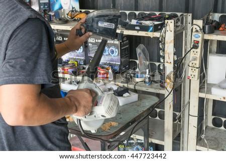 Bangkok, Thailand - March 20, 2016 : Unidentified serviceman checking headlight in a car at garage - stock photo