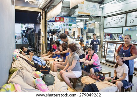 BANGKOK, THAILAND - MARCH 15 : Unidentified tourists gets massage with Thai traditional techniques at Jatujak Market on March 15, 2015 in Bangkok, Thailand. Jatujak is the largest market in Thailand. - stock photo