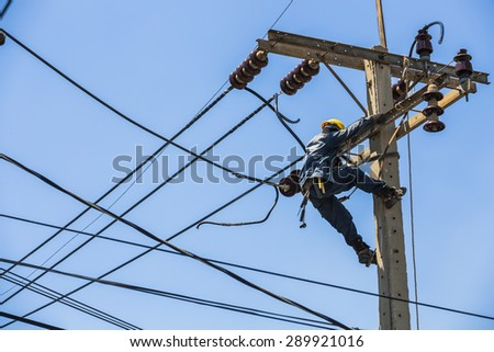 Bangkok, Thailand - May 16, 2015: Electrician hanging on the electricity pole to replace the electrical insulator