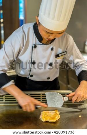 Bangkok, Thailand - 7 May 2016 - Female chef slices delicious chicken teriyaki to serve the customer in a teppanyaki kitchen. - stock photo
