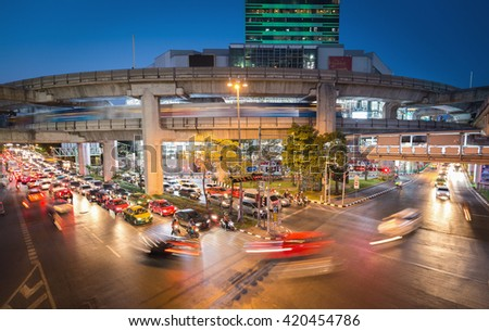 Bangkok, Thailand - May 10, 2016: Movement of cars in a traffic in Bangkok (called Siam) after sunset. There was a moving skytrain on the rail above the road. - stock photo