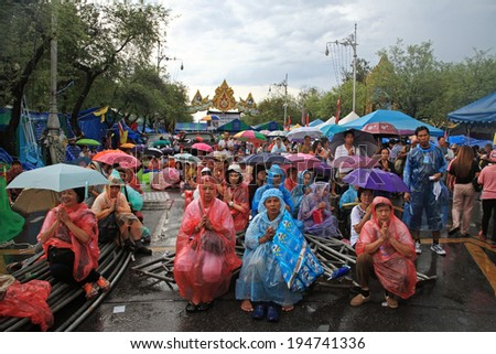BANGKOK, THAILAND - MAY 13, 2014: Thai protestors, called PDRC, with raincoats or umbrellas gather at Ratchadamneon street to pray during raining on Visakha Bucha day to reform the country. - stock photo