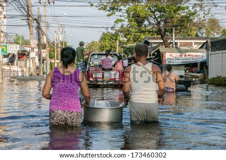 Bangkok - Thailand, Nov 6, 2011: A woman and her husband carrying a food for their child along Soi Chinnakhet, Ngamwongwan road during a big flooding in Thailand - stock photo