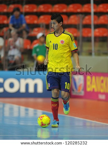 BANGKOK, THAILAND-NOV 18: Angellote Caro of Colombia (y) runs with the ball during the FIFA Futsal World Cup between Italy and Colombia at Indoor Stadium Huamark on Nov18,2012 in Bangkok,Thailand. - stock photo