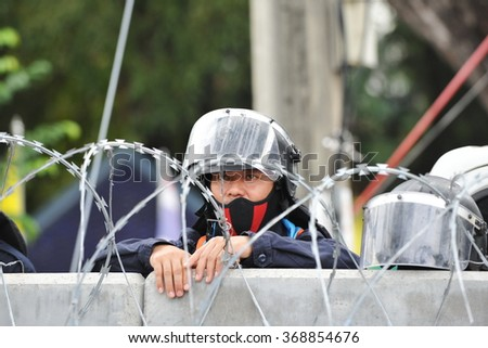 BANGKOK, THAILAND - NOV 24, 2013: Riot police officers stand guard near parliament during an anti government rally. Over 30,000 police are deployed at government sites amid ongoing street protests. - stock photo