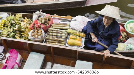 BANGKOK, THAILAND - November 5, 2016: Aged woman selling a variety of fruit on the floating market in Bangkok, Thailand