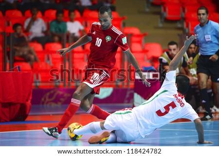 BANGKOK,THAILAND-NOVEMBER 05:Aziz Derrou (red) of Morocco runs with the ball during the FIFA Futsal World Cup between Morocco and Iran at Indoor Stadium Huamark on Nov5, 2012 in Bangkok,Thailand. - stock photo