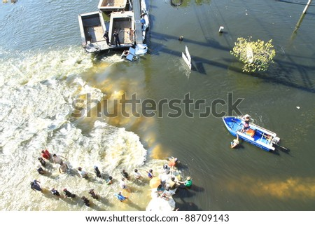 BANGKOK, THAILAND - NOVEMBER 13: Boat is passing through water barrier after barrier are destroyed during the worst monsoon flooding in decades in Bangkok, Thailand on November 13, 2011. - stock photo