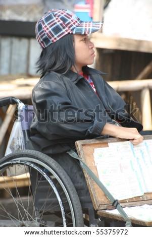BANGKOK, THAILAND - NOVEMBER 29: Disabled lady sells lottery tickets in Chatuchak market on November 29, 2008 in Bangkok. - stock photo