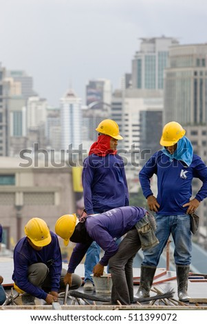 Bangkok, Thailand - November 10 2008 :  In a construction site in Bangkok, women and men work on metal structure. Salaries are very low for a dangerous and tiring work.
