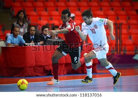 BANGKOK,THAILAND-NOVEMBER 03:Ramadan Samasry (red) of Egypt runs with the ball during the FIFA Futsal World Cup between Egypt and Serbia at Indoor Stadium Huamark on Nov3,2012 in Bangkok,Thailand. - stock photo