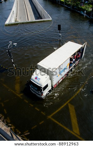 BANGKOK THAILAND – NOVEMBER 13: Truck carries a group of people to evacuate from the flooded area at Phahon Yothin Road during the massive flood crisis on November 13, 2011 in Bangkok, Thailand. - stock photo