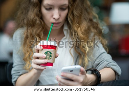 BANGKOK, THAILAND - NOVEMBER 16, 2015: Young business woman with hot beverage inside Starbucks coffee store. Starbucks is the largest coffeehouse company in the world. - stock photo