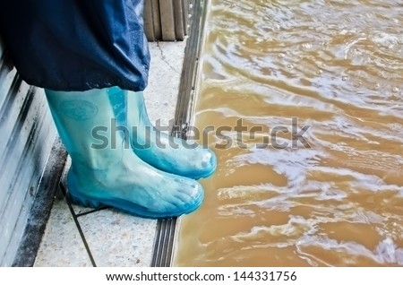 BANGKOK, THAILAND - OCT 29: Unidentified people with rubber boot try to escape from flood during the worst flooding on October 29, 2011 in Bangkok, Thailand - stock photo