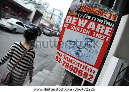BANGKOK, THAILAND - OCT 3, 2013: View of a sign warning of bag theft crime. The Thai capital is notorious for its motorbike robbery gangs and street crime.  - stock photo