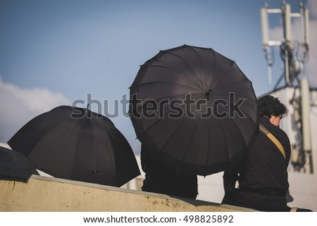 Bangkok, Thailand- October 14, 2016: A man hold the umbrella waiting a convoy carrying the body of the King from Siriraj Hospital to the Royal Palace.