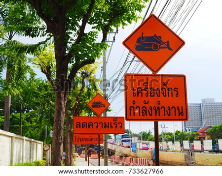 "BANGKOK, THAILAND - OCTOBER 11, 2007: Red orange multiple sign pole with construction crane icon and Thai words ""Machines are working"", and ""Reduce speed"", beside the bridge, and street trees"