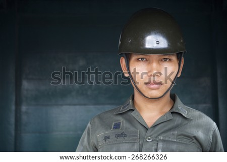 BANGKOK, THAILAND - OCTOBER 26, 2014: Young Thai Army soldier stands guard outside the Grand Palace. Royal Guards serve as protectors to the Royal Family. - stock photo