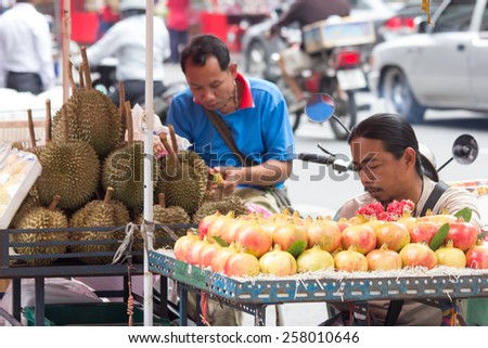 Bangkok, Thailand-Sep 17th 2012: Fruit vendors waiting for customers. Street vendors can be found all over the city. - stock photo