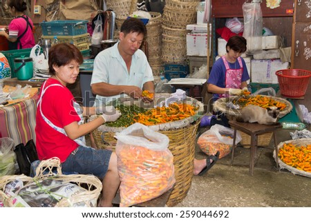 bangkok, Thailand-Sep 25th 2012: Sorting chillies in Pak Khlong Talad vegetable market. This is the largest wholesale fruit and vegetable market in Thailand. - stock photo