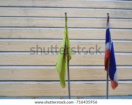 BANGKOK, THAILAND - SEPTEMBER 15, 2017: Old dirty flag poles of red, blue, white Thailand national and yellow with royal family emblem, folded, with pale brown wooden board tile wall background