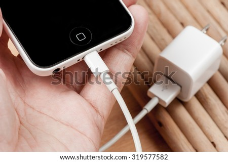 BANGKOK, THAILAND - SEPTEMBER 23, 2015: The iPhone5C connecting with the charger cable. - stock photo