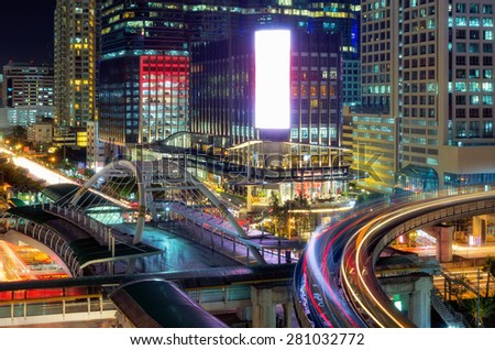 Bangkok view of a modern building at night. Traffic in the business district The Skytrain station Chong Nonsi. - stock photo
