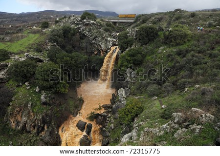 Banias Falls in the winter at the Golan Heights (Israel). Orange color of water because of washout of the earth from fields as a result of heavy rains. - stock photo