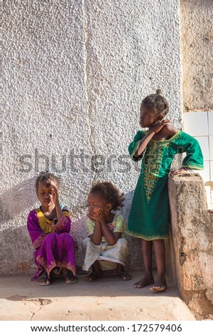 BANJUL, GAMBIA - MAR 14, 2013: Three unidentified Gambian girls play in the street in Gambia, Mar 14, 2013. Major ethnic group in Gambia is the Mandinka - 42%