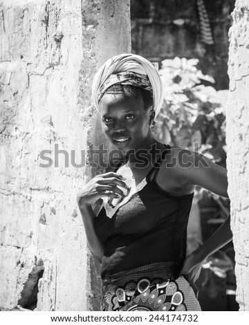 BANJUL, GAMBIA - MAR 14, 2013: Unidentified Gambian beautiful woman stays near the wall in Gambia, Mar 14, 2013. People of Gambia suffer of poverty due to the unstable economical situation - stock photo