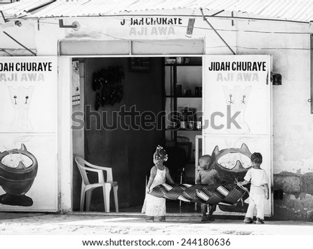 BANJUL, GAMBIA - MAR 14, 2013: Unidentified Gambian children play together at the shop of their father inGambia, Mar 14, 2013. Major ethnic group in Gambia is the Mandinka - 42% - stock photo