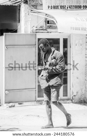 BANJUL, GAMBIA - MAR 14, 2013: Unidentified Gambian lonely man walks in Gambia, Mar 14, 2013. Major ethnic group in Gambia is the Mandinka - 42% - stock photo