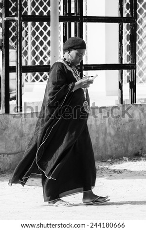 BANJUL, GAMBIA - MAR 14, 2013: Unidentified Gambian woman in a black suit seaks on phone in Gambia, Mar 14, 2013. Major ethnic group in Gambia is the Mandinka - 42% - stock photo