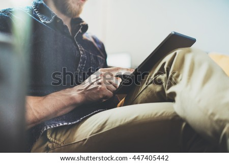Bank account manager reading business news modern Interior Design Loft Office.Man relax Vintage Sofa,Use contemporary tablet,share information.Blurred Background.New Startup Idea Process.Closeup - stock photo