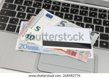 bank card, euro cash, laptop - stock photo