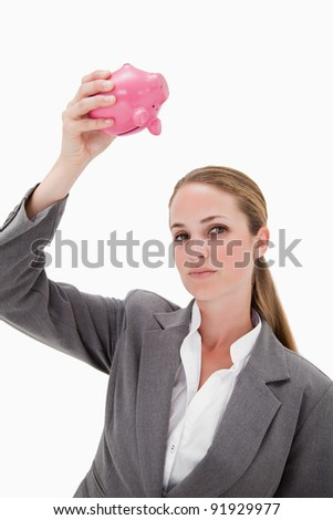 Bank employee holding piggy bank over her head against a white background - stock photo