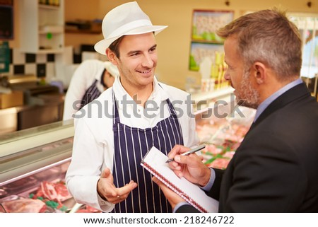 Bank Manager Meeting With Owner Of Butchers Shop - stock photo