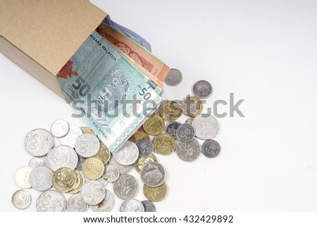 Bank notes in the box and coins  isolated on wooden table. Business concept. DOF and copy space.