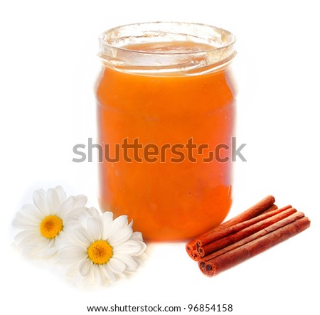 Bank of honey from flowers of chamomile and cinnamon - stock photo