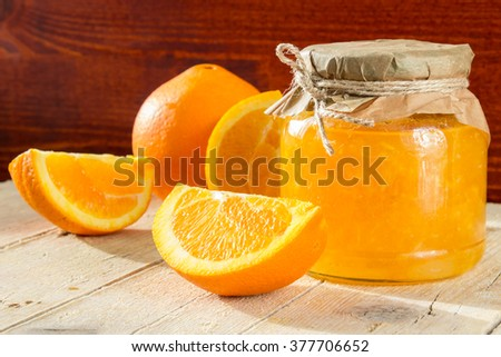 Bank of orange marmalade and slices of orange on a wooden background - stock photo