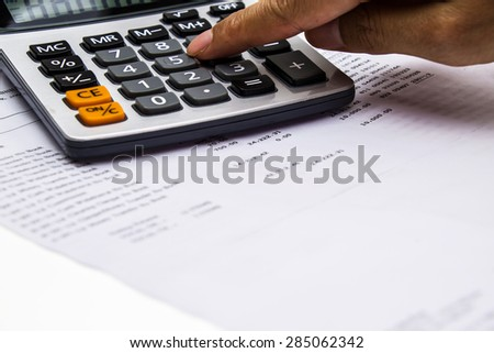 bank statement and calculator with finger pressing - stock photo