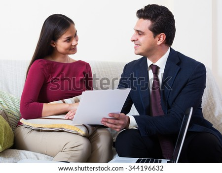 Banking agent showing contract to female client in domestic interior - stock photo