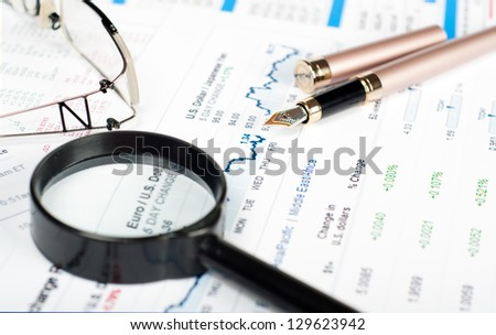 Banking business or financial analytics desktop with accounting charts, pen and glasses