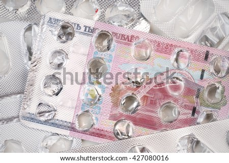 Banknote 10000 Belarusian rubles on an empty blister pack of tablets - stock photo